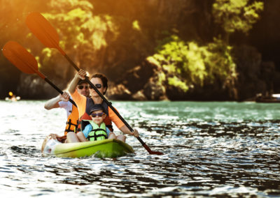 Happy family kayaking at tropical islands